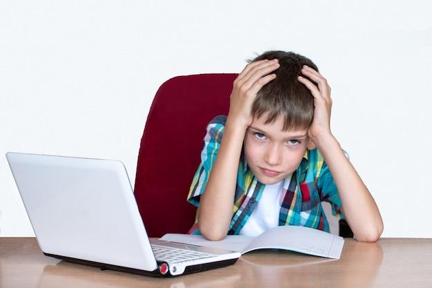 Ragazzo stanco che tiene la sua testa per fare i compiti, un ragazzo che ha problemi con i compiti