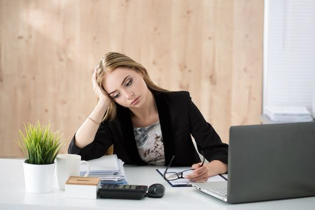 Donna stanca di affari che si siede al suo posto di lavoro. superlavoro, lavoro straordinario e stress sul concetto di lavoro.