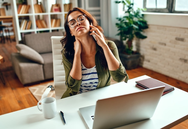 Una donna d'affari stanca e stressata lavora al laptop mentre è seduta a un tavolo a casa e parla al telefono. libero professionista, lavoro da casa.