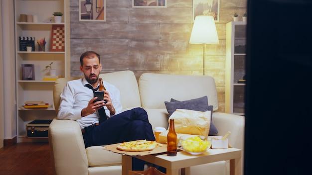 Uomo d'affari stanco dopo una lunga giornata di lavoro navigando al telefono e bevendo birra. cibo spazzatura.