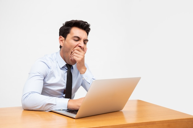 Uomo d'affari stanco esaurito e sbadiglio dopo duro lavoro e carico di lavoro eccessivo isolato su bianco
