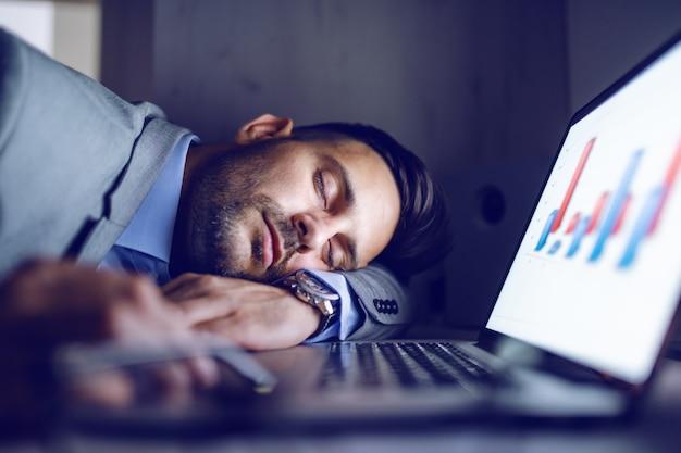 Uomo d'affari stanco che dorme nel suo ufficio.