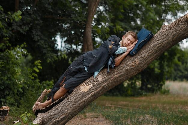 Uomo d'affari stanco in vestito strappato che dorme sull'albero sull'isola deserta. rischio aziendale, crollo o concetto di fallimento