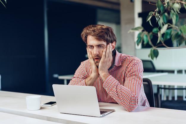 Uomo d'affari stanco che lavora al suo computer nell'ufficio dello spazio aperto. fine della giornata lavorativa