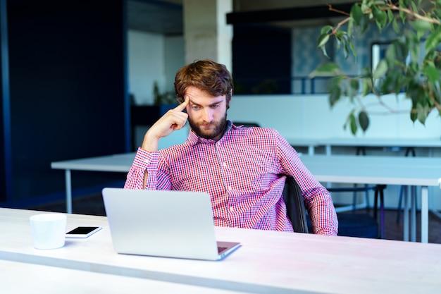 Uomo d'affari stanco che lavora al suo computer nell'ufficio dello spazio aperto