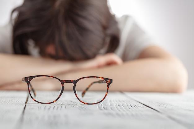 Imprenditrice stanca addormentarsi nel suo posto di lavoro con gli occhiali, le donne d'affari si sentono scoraggiate tenendo gli occhiali