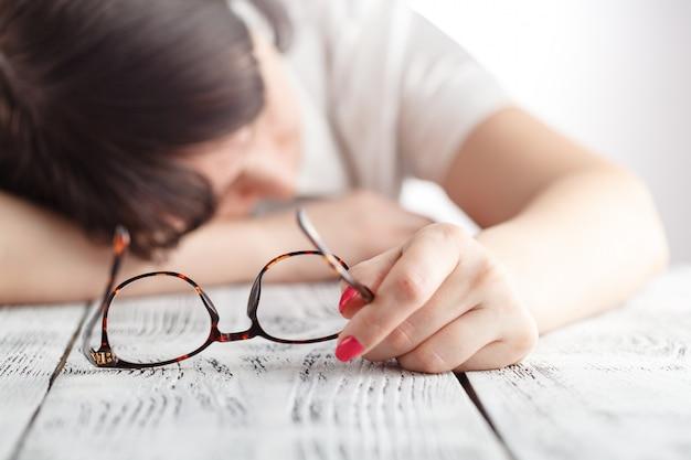 Donna di affari stanca addormentarsi nel suo luogo di lavoro con gli occhiali