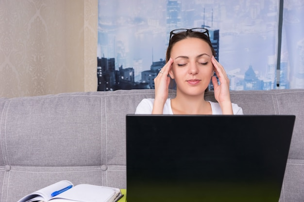 Donna d'affari stanca che fa un massaggio alla testa mentre lavora su un laptop e fa i suoi affari da casa seduta su un divano