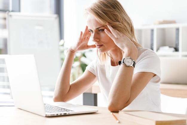 Donna di affari faticosa che lavora al computer portatile