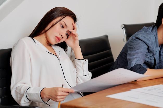 Donna di affari stanca che lavora con i documenti