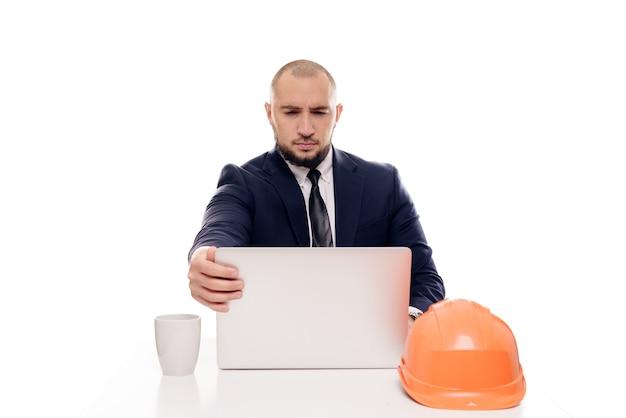 Un uomo d'affari stanco del costruttore in un casco arancione guarda lo schermo del laptop e studia il progetto di costruzione. si siede a tavola e beve il caffè, nervoso