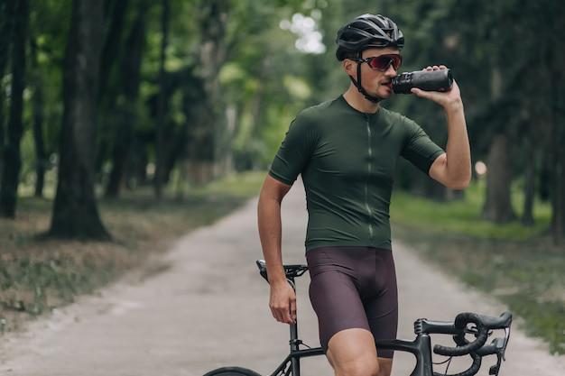 Acqua potabile del ciclista stanco dopo un'intensa corsa all'aperto.