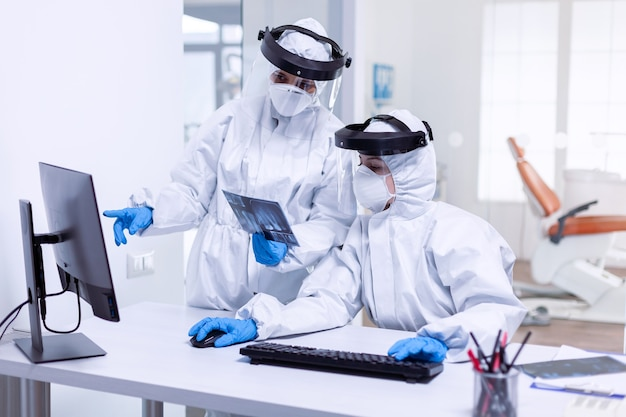 Squadra stanca di odontoiatria vestita con tuta in dpi durante il covid-19. specialista medico che indossa indumenti protettivi contro il coronavirus durante l'epidemia globale guardando la radiografia nello studio dentistico.