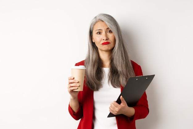 Imprenditrice asiatica stanca e delusa con i capelli grigi, bere il caffè in un bicchiere di carta e guardando cupo alla telecamera, in piedi su sfondo bianco.