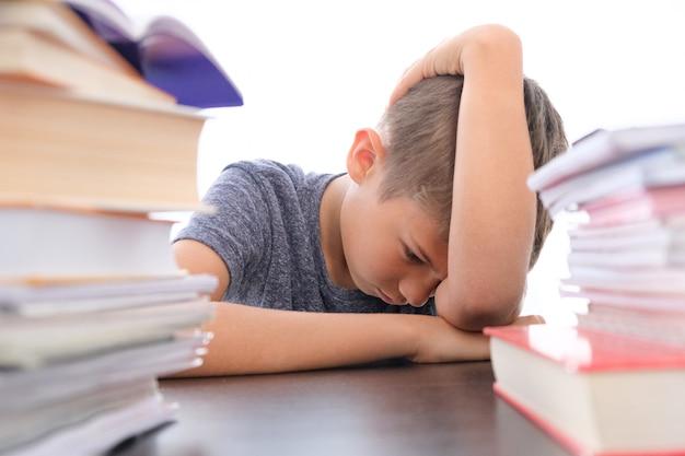 Bambino deluso stanco seduto tra una pila di libri