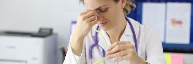 Medico stanco che si siede al tavolo nel suo ufficio e si prende cura dei suoi occhi