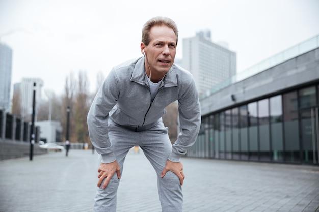 Corridore anziano stanco in abiti sportivi grigi in piedi sulla strada. vista frontale