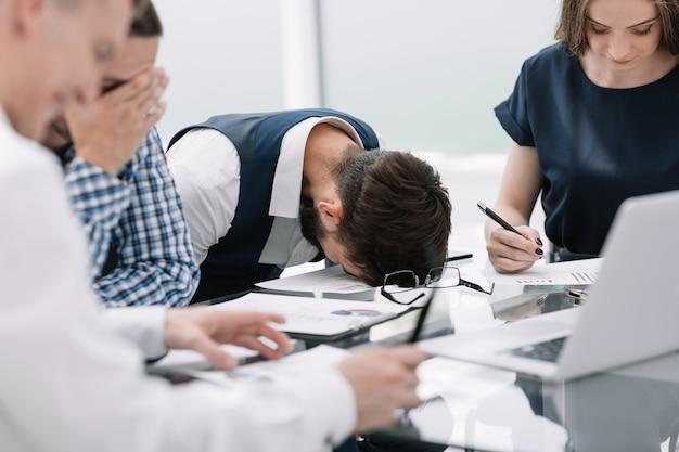 Impiegato stanco a una riunione di lavoro in ufficio