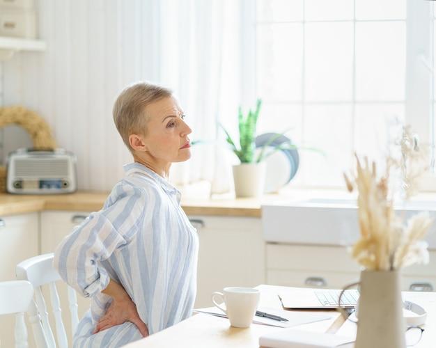 Stanca esausta donna d'affari di mezza età che si massaggia la schiena mentre è seduta in cucina e lavora
