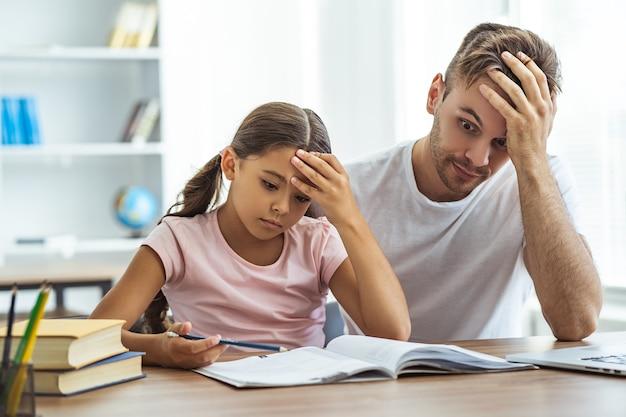 Il padre stanco e una figlia che fanno i compiti a tavola