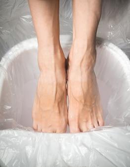Piedi stanchi, piedi femminili in un bagno rilassante.
