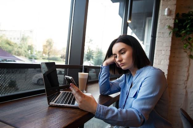 Libero professionista femminile stanco che lavora nella caffetteria. concetto di problemi di concentrazione. sconvolto giovane donna che guarda nello smartphone e in attesa di una chiamata. atmosfera accogliente da caffetteria. caffè o ristorante sullo sfondo.