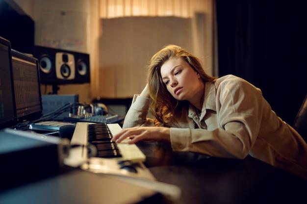 Ingegnere del suono femminile stanco in cuffie, interni di studio di registrazione sullo sfondo. sintetizzatore e mixer audio, posto di lavoro per musicisti, difficile processo creativo