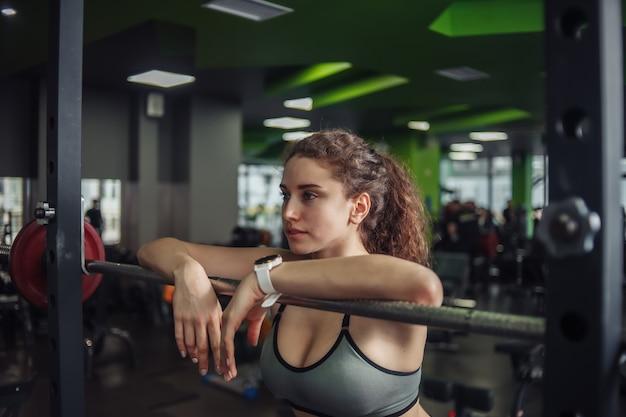 Donna in forma stanca in abiti sportivi che si appoggia sul bilanciere in palestra