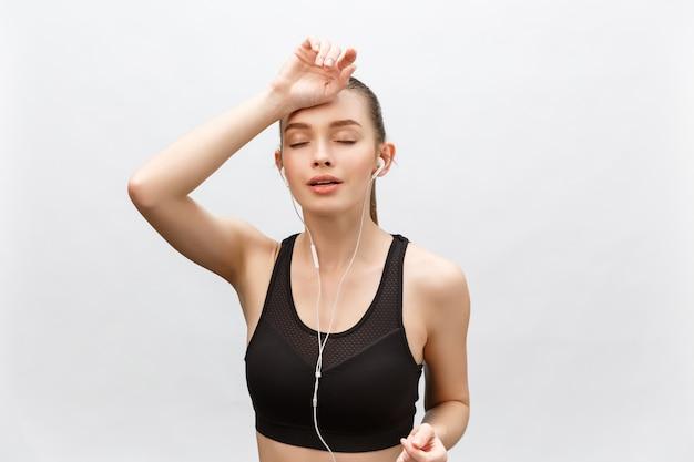 Donna stanca di fitness sudorazione prendendo una pausa ascoltando musica sul telefono dopo un allenamento difficile.