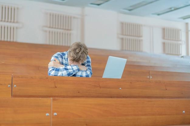 Stanco del sonno dello studente di studio in aula magna