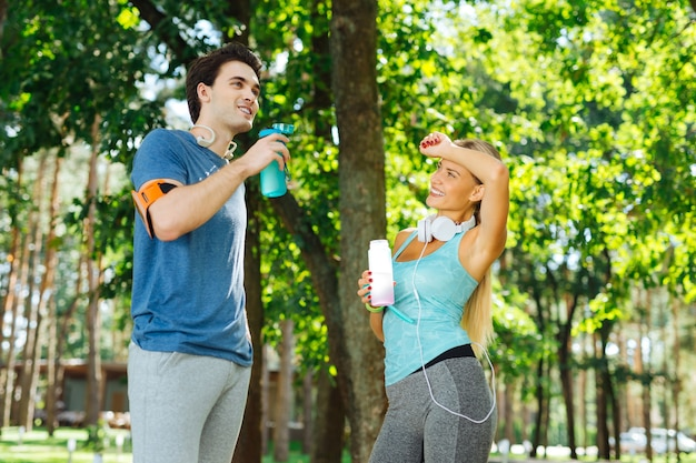 Stanchi dall'allenamento. giovane donna positiva che tiene la sua mano mentre levandosi in piedi con il suo ragazzo dopo un allenamento