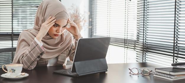 Stanco frustrato giovane musulmano donna d'affari marrone hijab sensazione stressato tenendo la testa con le mani, concetto di fallimento problema aziendale