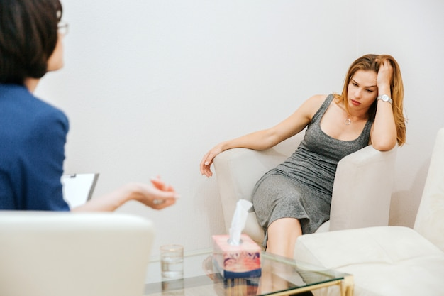 La ragazza stanca sta sedendosi sul sofà e sta ascoltando il terapista. è disperata. la ragazza sta guardando in basso e tenendo la testa con la mano. il dottore le sta parlando.