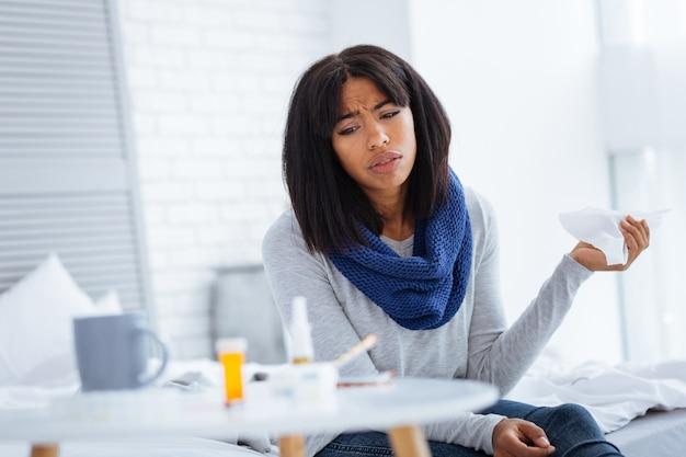 Sguardo stanco. donna stanca dispiaciuta triste guardando la grande varietà di pillole e miscele sul suo tavolino bianco