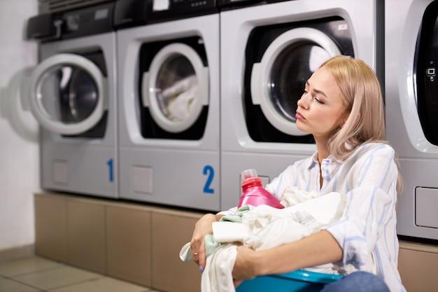 Casalinga 20s stanca che trasporta cesto della biancheria con vestiti sporchi in attesa della fine del lavaggio, seduta sul pavimento di cattivo umore, esausta. in casa di lavaggio