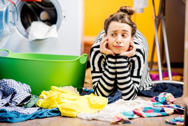 Casalinga stanca sdraiata per terra con molti vestiti vicino alla lavatrice di casa