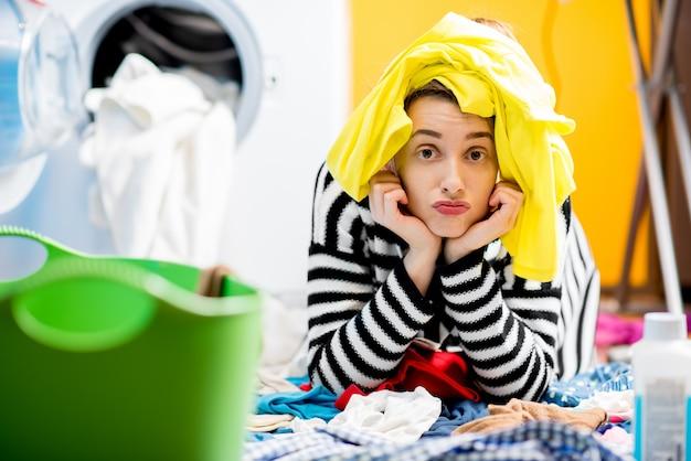 Casalinga stanca seduta per terra vicino alla lavatrice con vestiti colorati a casa