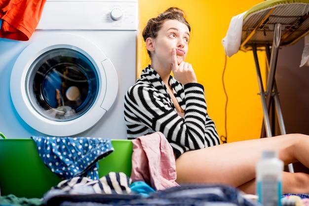 Casalinga stanca seduta vicino alla lavatrice con vestiti colorati a casa