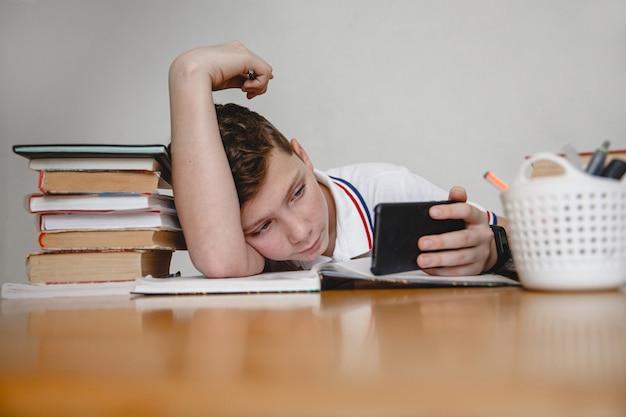 Stanco delle lezioni, un adolescente a casa per i libri di testo guarda uno smartphone