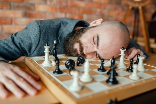 Giocatore di scacchi maschio stanco che dorme sul bordo.
