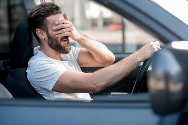 Uomo stanco vestito casual con una maglietta bianca alla guida di un'auto con mal di testa in città