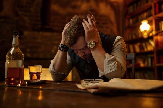 L'uomo stanco fuma sigarette e beve bevande alcoliche, libreria e interni ricchi di ufficio sullo sfondo. cultura del fumo di tabacco, sapore specifico