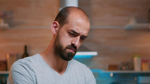 Uomo stanco che strizza gli occhi guardando lo schermo del laptop cercando di mettere a fuoco il concentrato. impiegato impegnato e concentrato che utilizza la moderna rete di tecnologia wireless che fa gli straordinari per il lavoro che legge la scrittura, la ricerca