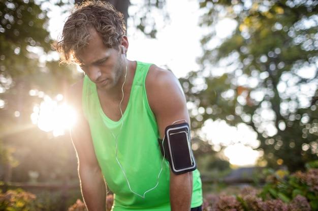 Uomo stanco che respira profondamente mentre fa jogging