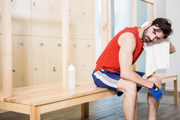 Uomo stanco che asciuga sudore con l'asciugamano nello spogliatoio