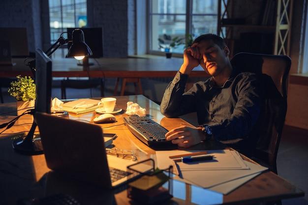 Stanco. uomo che lavora in ufficio da solo durante la quarantena del coronavirus o del covid-19, rimanendo fino a tarda notte. giovane uomo d'affari, manager che svolge attività con smartphone, laptop, tablet in un'area di lavoro vuota.