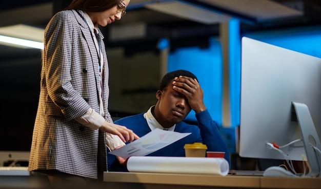 I manager stanchi lavorano nell'ufficio notturno