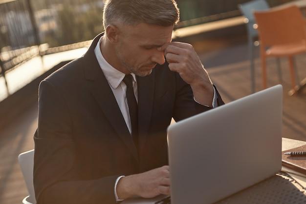 Stanco uomo d'affari maturo che fa massaggiare il naso mentre lavora sul laptop all'aperto