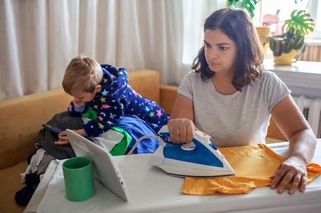 La mamma stanca guarda il video sul tablet e stira le cose accanto al figlio anche con lo smartphone