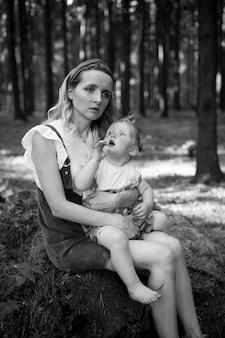 Madre stanca in posa con suo figlio divertente nella foresta